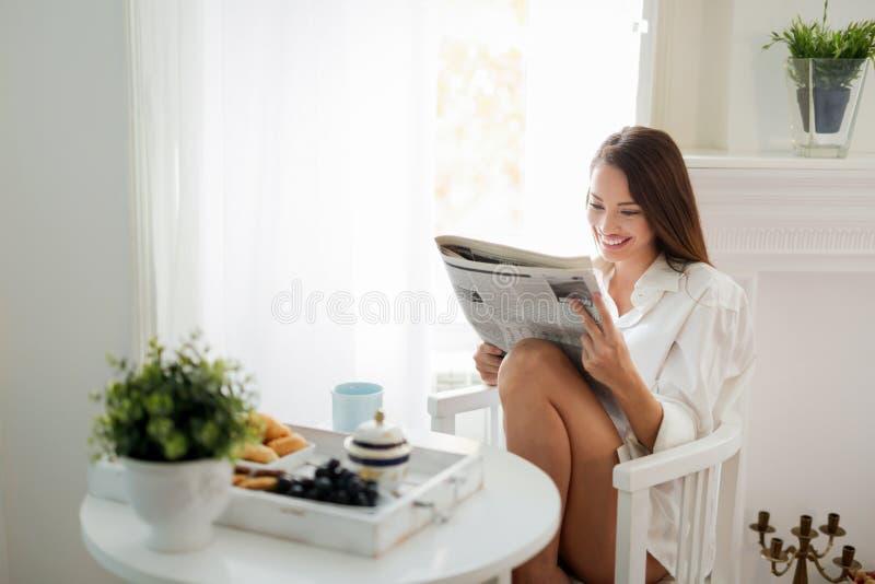 Het mooie jonge tijdschrift van de vrouwenlezing thuis stock foto's