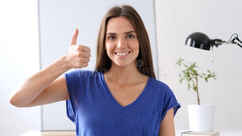 Het mooie jonge vrouw gesturing beduimelt omhoog stock afbeeldingen