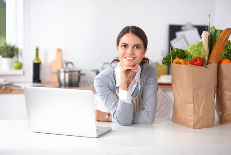 Het mooie jonge vrouw koken die laptop het scherm met ontvangstbewijs in de keuken bekijken royalty-vrije stock foto's