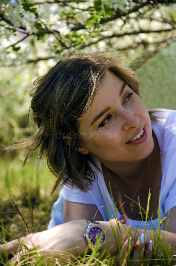 Het mooie Jonge Vrouw liggen op een gebied, een groene gras en een paardebloem bloeit Geniet in openlucht van Aard Gezond Glimlac stock afbeelding