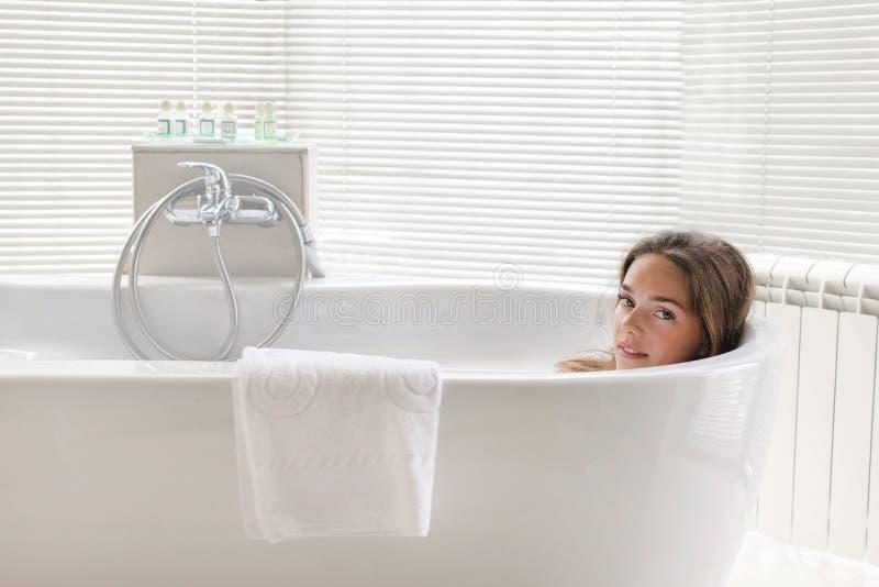 Het mooie jonge vrouw ontspannen die in bathtube liggen royalty-vrije stock foto's