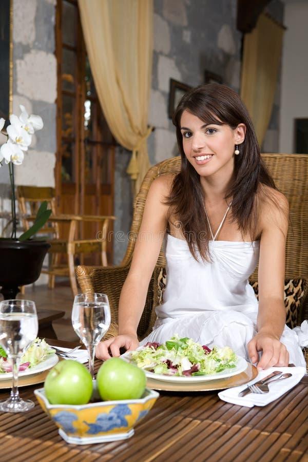 Het mooie jonge vrouw ontspannen eten stock afbeelding