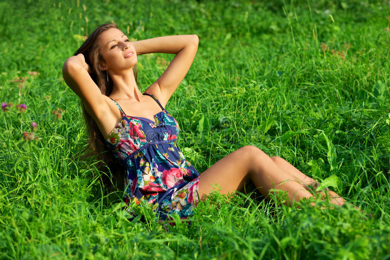 Het mooie jonge vrouw ontspannen in gras royalty-vrije stock afbeelding