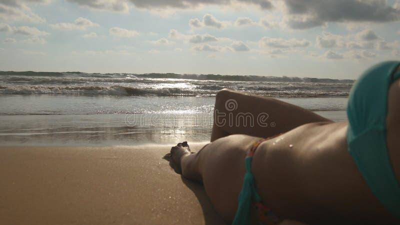 Het mooie jonge vrouw ontspannen op overzeese kust tijdens de reis van de de zomervakantie Oceaangolven die meer dan gelooide vro royalty-vrije stock foto's