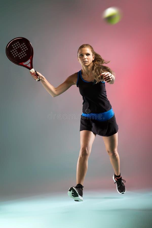 Het mooie jonge vrouw spelen padel binnen over multicolored achtergrond stock foto