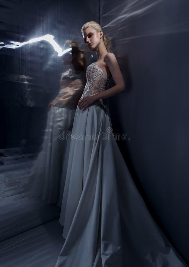 Het mooie jonge vrouw stellen in een huwelijkskleding stock foto's