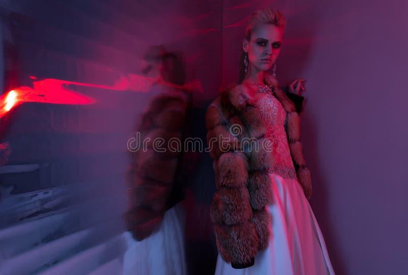 Het mooie jonge vrouw stellen in een huwelijkskleding in blauw rood, stock fotografie