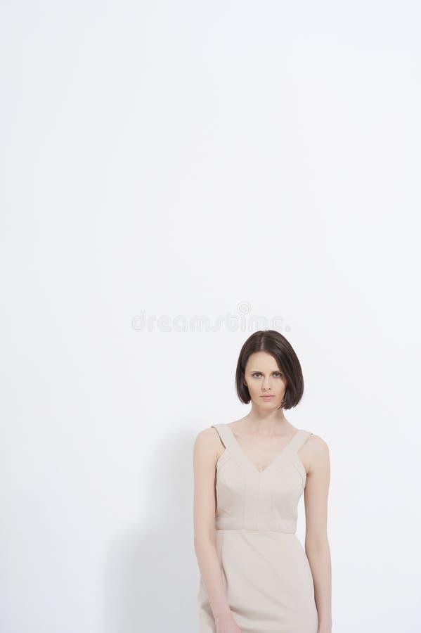 Het mooie jonge vrouw stellen in kleding stock afbeeldingen