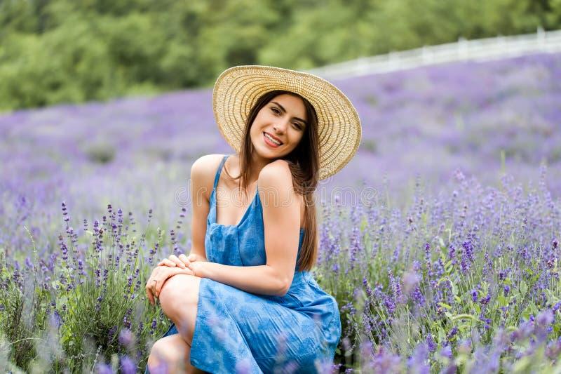 Het mooie jonge vrouw stellen in lavendel royalty-vrije stock afbeeldingen