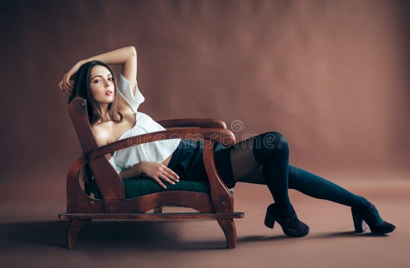 Het mooie jonge vrouw stellen op bank op bruine achtergrond Fashio stock afbeeldingen