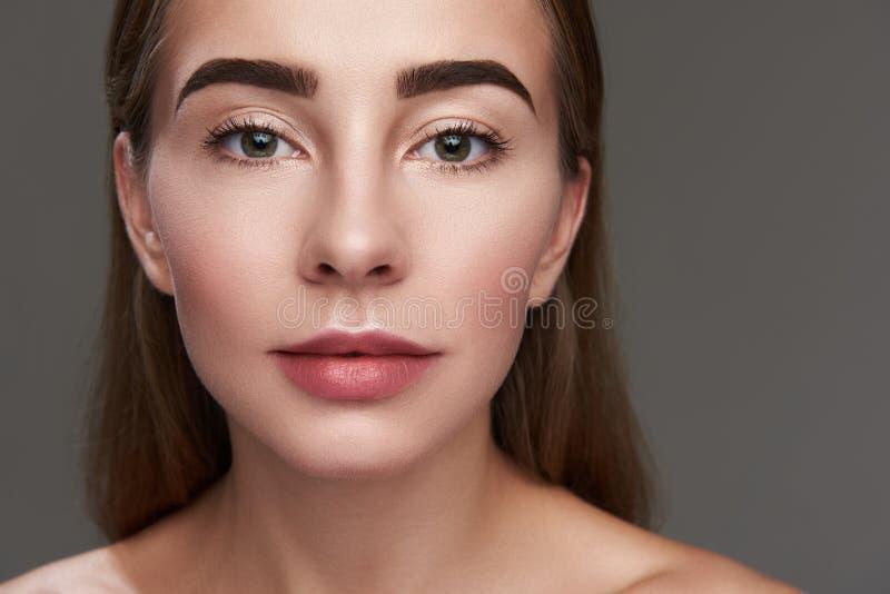Het mooie jonge vrouw stellen op grijze achtergrond stock afbeeldingen