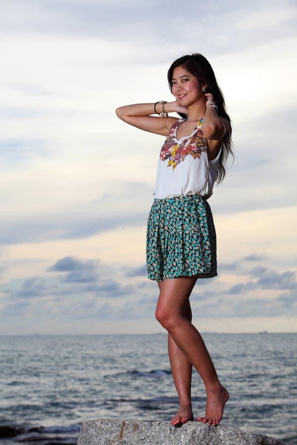 Het mooie jonge vrouw stellen op stenen dichtbij overzees royalty-vrije stock fotografie