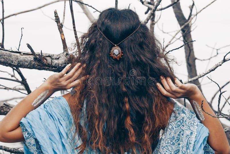 Het mooie jonge vrouw stellen van de rug in openlucht heksenambacht stock foto's