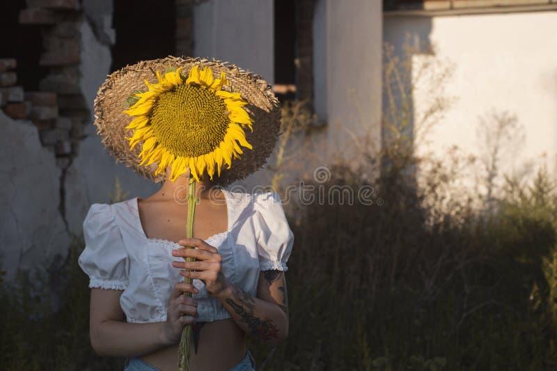 Het mooie jonge vrouw verbergen achter een zonnebloem stock afbeeldingen
