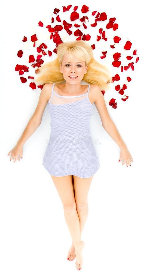Het mooie jonge vrouw werpen nam bloemblaadjes toe stock afbeelding