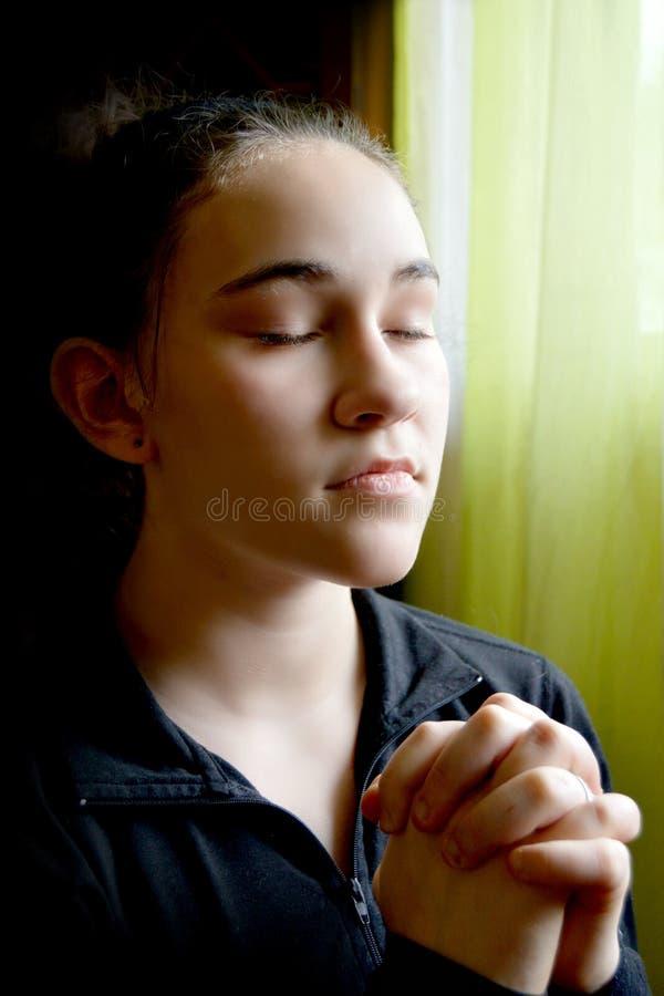Het mooie jonge vrouwelijke bidden stock foto