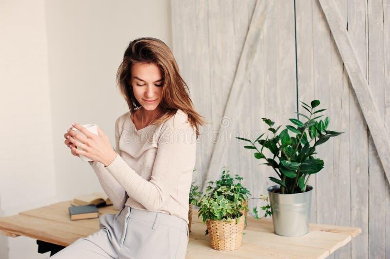het mooie jonge vrouwelijke vrouw ontspannen thuis in luie weekendochtend met kop van koffie royalty-vrije stock afbeeldingen