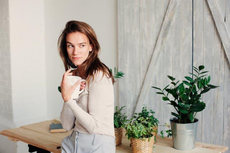 het mooie jonge vrouwelijke vrouw ontspannen thuis in luie weekendochtend met kop van koffie stock fotografie