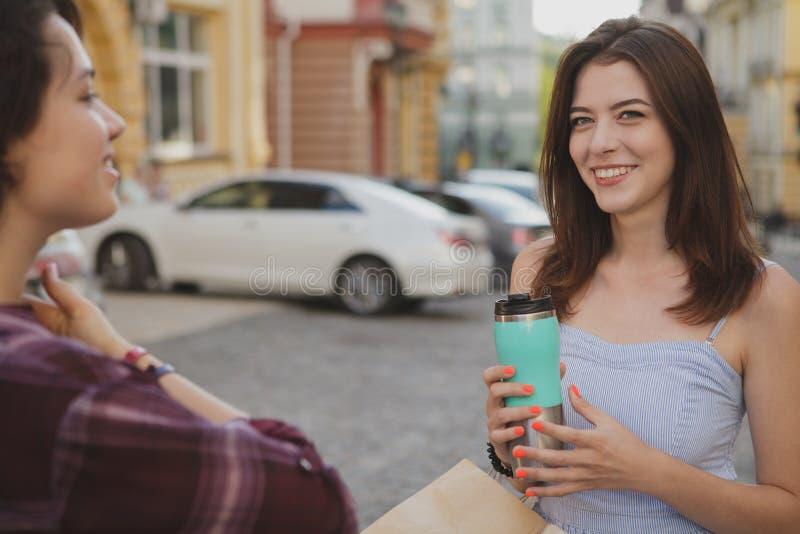 Het mooie jonge vrouwen genieten die stadsstraten samen na het winkelen lopen royalty-vrije stock afbeeldingen