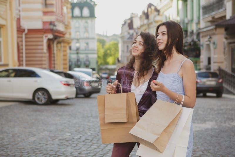 Het mooie jonge vrouwen genieten die stadsstraten samen na het winkelen lopen stock foto's