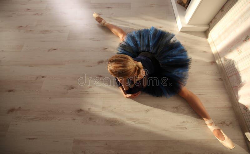 Het mooie Jonge Vrouwenballerina Uitrekkende die Opwarmen in huisbinnenland, op houten vloer wordt verdeeld royalty-vrije stock foto's