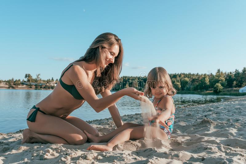 Het mooie jonge vrouwenmamma spelen op kust van een meer met zand, naast een klein kind is een dochter, het gelukkige glimlachen, royalty-vrije stock foto's
