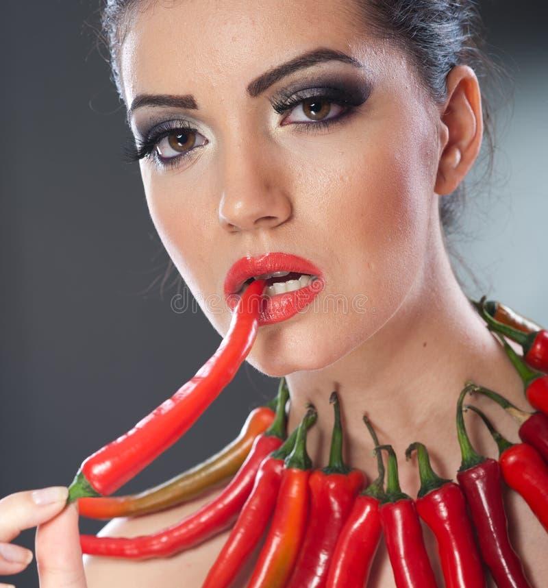 Het mooie jonge vrouwenportret met roodgloeiende en kruidige peper, mannequin met creatieve voedselgroente maakt omhoog stock fotografie