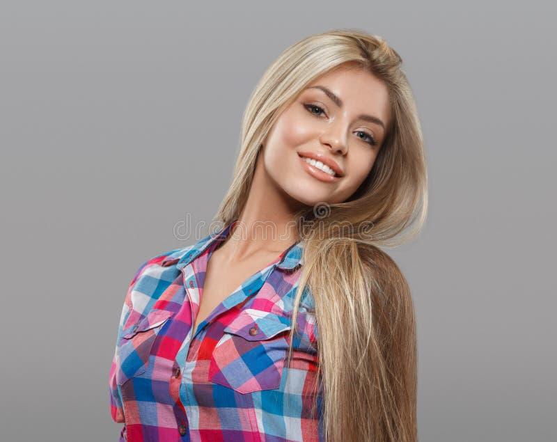 Het mooie jonge vrouwenportret stellen aantrekkelijk met verbazend lang blondehaar stock foto