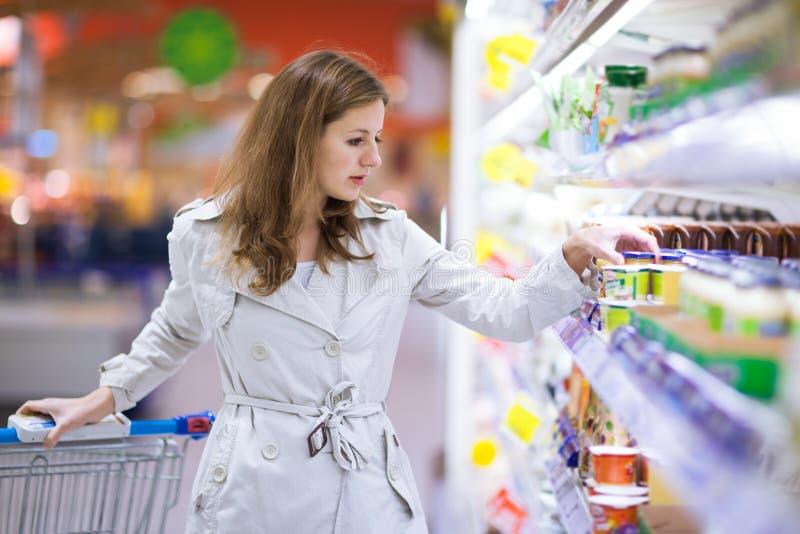 Het mooie jonge womanshopping in supermarkt royalty-vrije stock foto's