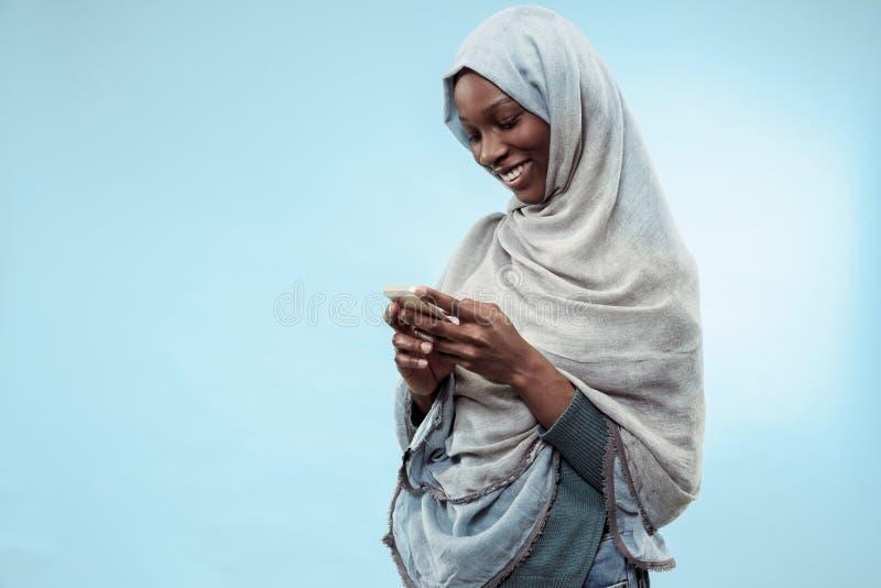 Het mooie jonge zwarte moslimmeisje die grijze hijab, met een gelukkige glimlach op haar gezicht dragen stock afbeelding
