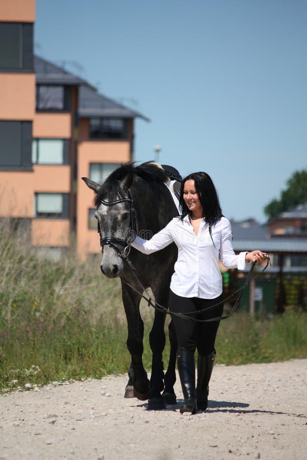 Het mooie Kaukasische jonge vrouw en paard lopen royalty-vrije stock afbeelding