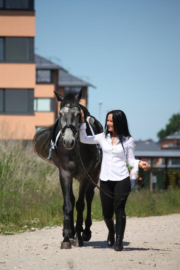 Het mooie Kaukasische jonge vrouw en paard lopen stock foto