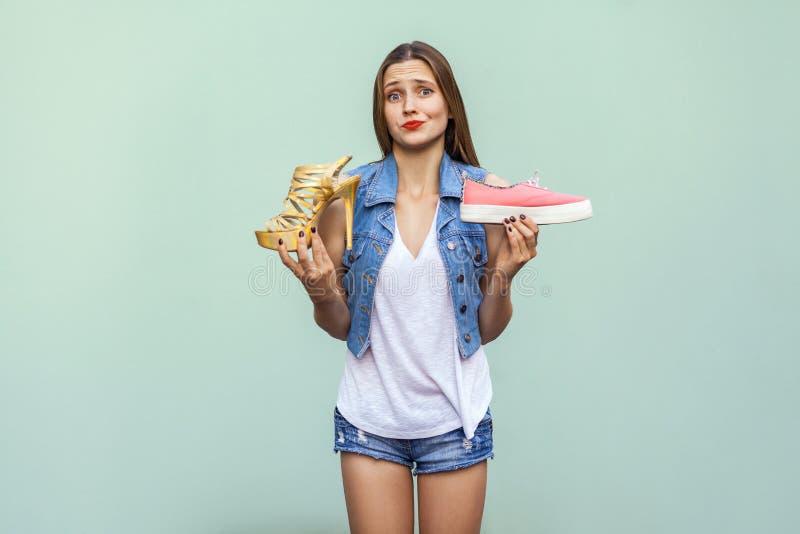 Het mooie Kaukasische toevallige meisje met sproeten kreeg het kiezen van comfortabele tennisschoenen of ongelegen maar knappe ho stock foto's