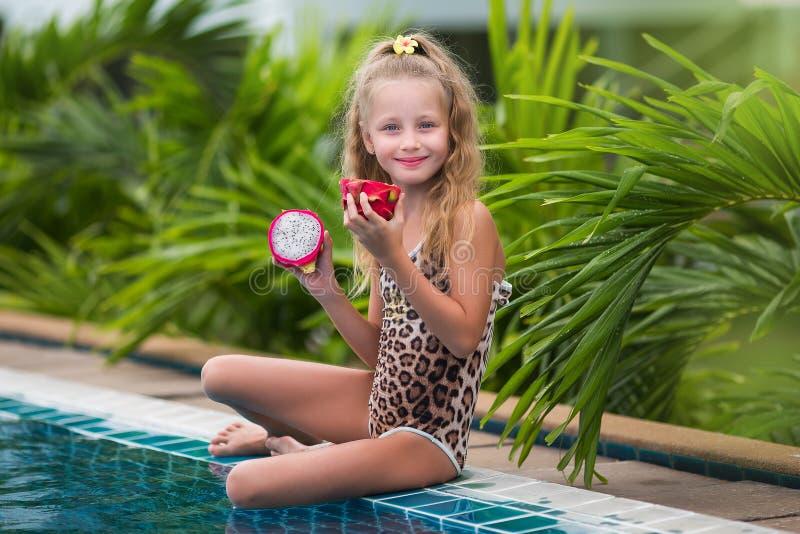 Het mooie kindmeisje spelen met draakfruit dichtbij een zwembad Tropische openluchtachtergrond De ruimte van het exemplaar royalty-vrije stock afbeelding