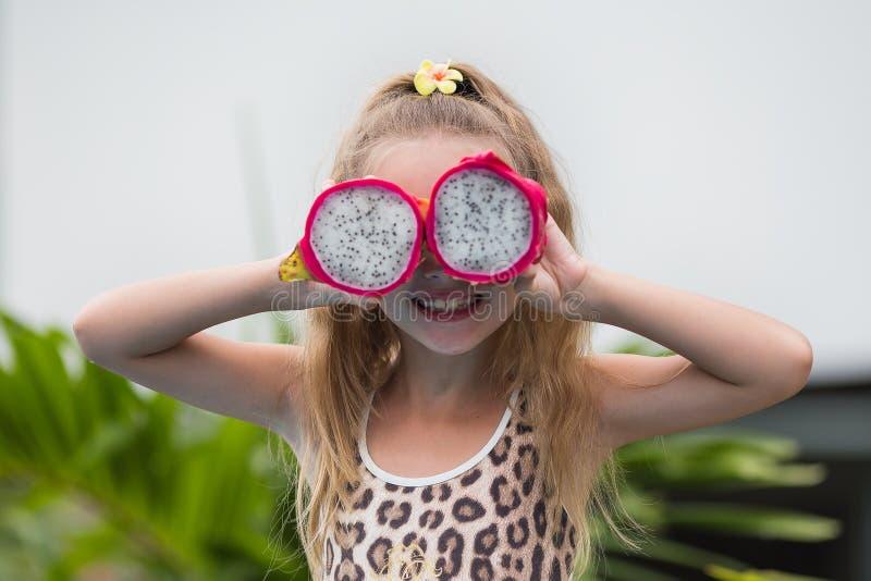 Het mooie kindmeisje spelen met draakfruit dichtbij een zwembad Tropische openluchtachtergrond De ruimte van het exemplaar royalty-vrije stock foto