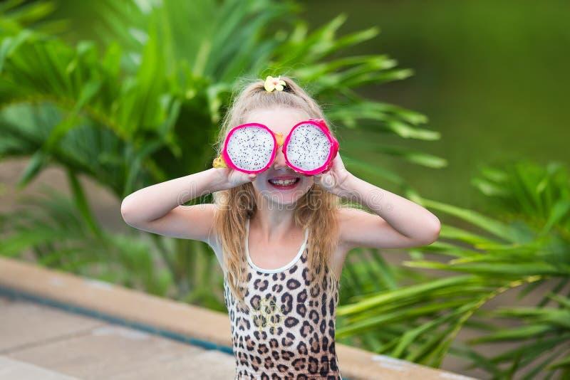Het mooie kindmeisje spelen met draakfruit dichtbij een zwembad Tropische openluchtachtergrond De ruimte van het exemplaar stock afbeeldingen