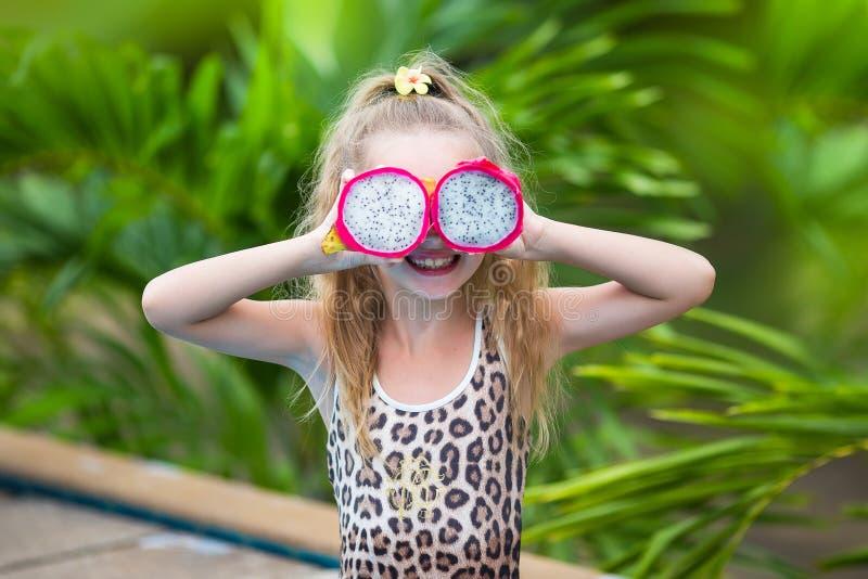 Het mooie kindmeisje spelen met draakfruit dichtbij een zwembad Tropische openluchtachtergrond De ruimte van het exemplaar royalty-vrije stock foto's