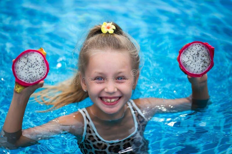 Het mooie kindmeisje spelen met draakfruit dichtbij een zwembad Tropische openluchtachtergrond De ruimte van het exemplaar royalty-vrije stock afbeeldingen