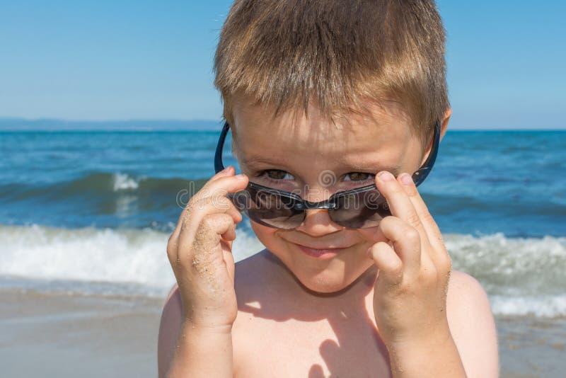 Het mooie kleine jongen stellen op een strand door het overzees met zonnebril stock foto's