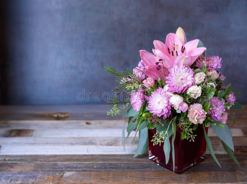 Het mooie kleurrijke roze boeket van de leliebloem op rustieke houten achtergrond royalty-vrije stock afbeeldingen