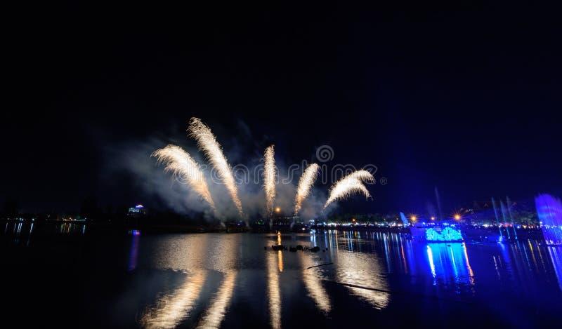 Het mooie kleurrijke vuurwerk toont op het stedelijke meer voor viering op donkere nachtachtergrond stock foto