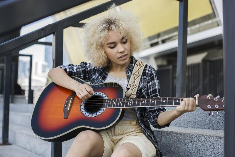 Het mooie, krullende Afrikaanse Amerikaanse meisje houdt van gitaar te spelen de straat stock foto