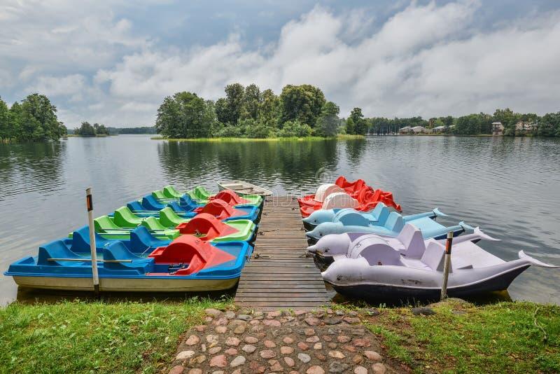 Het mooie landschap van de avondzomer van het meer en de toeristenboten van Trakai dichtbij houten pijler Meer en stormachtige he royalty-vrije stock foto