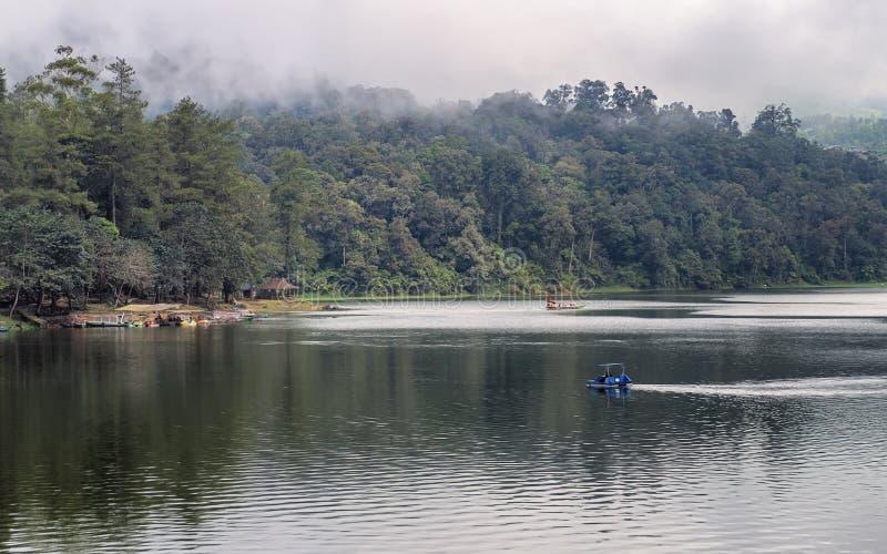 Het mooie landschap van reusachtig meer, met bomen, de huizen en de mist leiden het kalmeren tot atmosfeer stock foto's