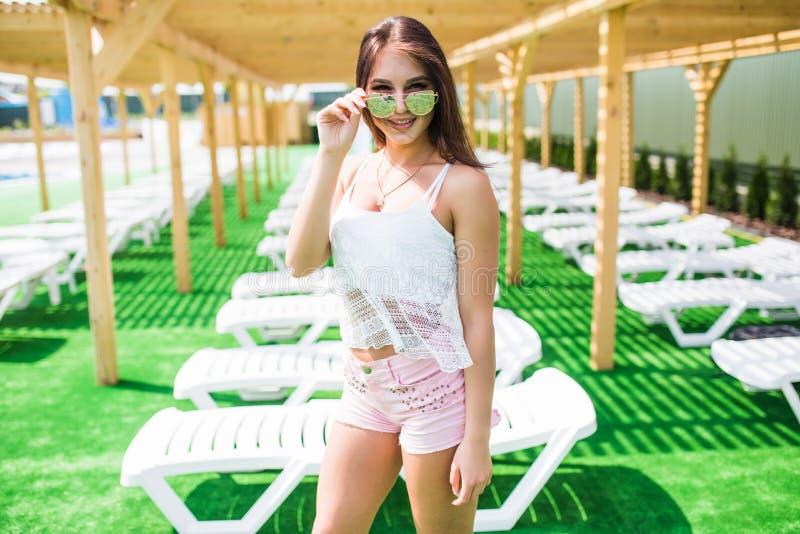 Het mooie lange haar vrouwelijke model stellen door de pool, openluchtportret Mooi sexy jong meisje met perfect slank cijfer met  royalty-vrije stock afbeeldingen