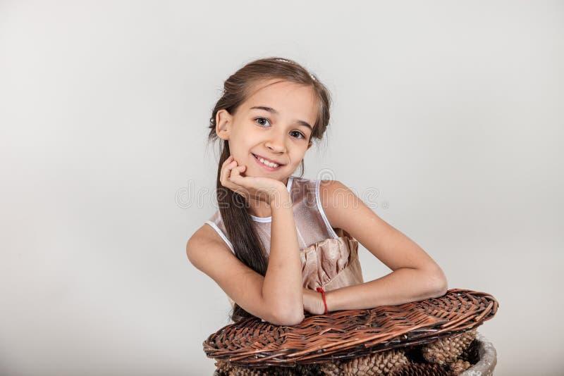 Het mooie langharige meisje glimlachen op haar gezicht zijn er verrukking en verrassing Het kind zit dichtbij de mand met sparapp stock fotografie