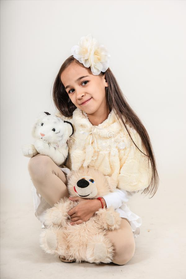 Het mooie langharige meisje kleedde zich in een witte laag Het kind houdt zacht speelgoed op geïsoleerde grijze achtergrond stock foto's