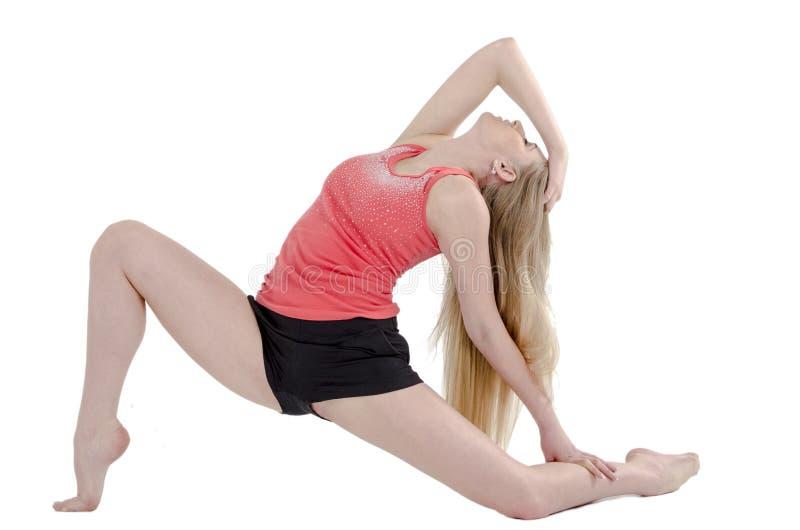 Het mooie langharige vrolijke meisje is bezig geweest met gymnastiek- oefeningen op de vloer stock afbeelding