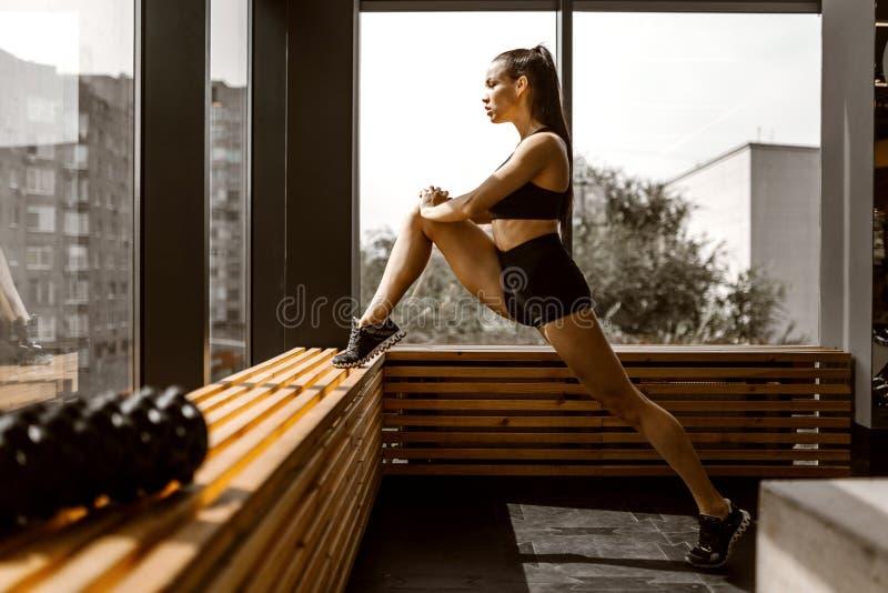 Het mooie lastermeisje gekleed in zwarte sportenbovenkant en borrels doet zich het uitrekken op een houten venstervensterbank in  stock fotografie