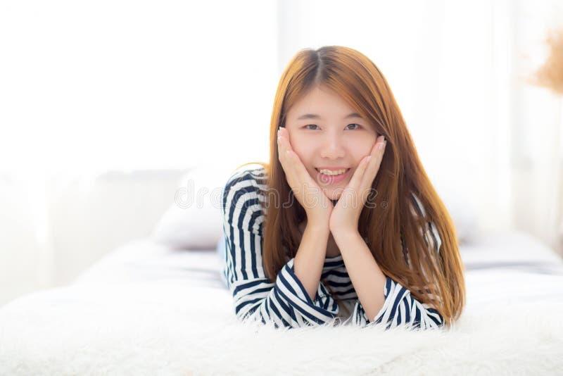 Het mooie liggen en de glimlach van de portret jonge Aziatische vrouw terwijl kielzog omhoog met zonsopgang bij ochtend royalty-vrije stock foto's